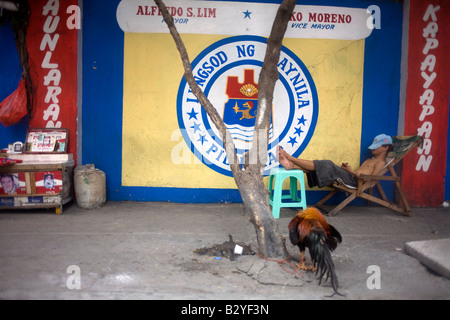A Filipino takes an afternoon nap on a sidewalk in Manila, Philippines. - Stock Image
