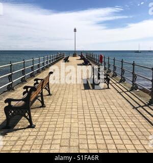 A pier on the seaside at the beach in swanage, Dorset, England. - Stock Image