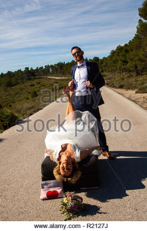 Couple of newlyweds pose with a sofa in the middle of a lonely road - Stock Image
