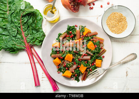 Boiled swiss chard with sweet potato, pomegranate and sesame seeds on a white wooden background. Top view - Stock Image