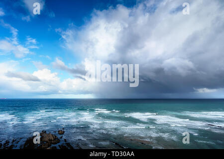 stormy clouds and heavy rain on a sea - Stock Image