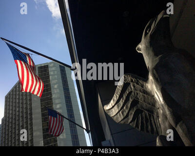 American flag and statue of mythical griffin outside hotel in downtown Miami, Florida. - Stock Image
