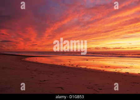 After sunset, the sky lights up. It reflects vibrant colors on the ocean, the cloudy sky and on the sand in Carlsbad, - Stock Image