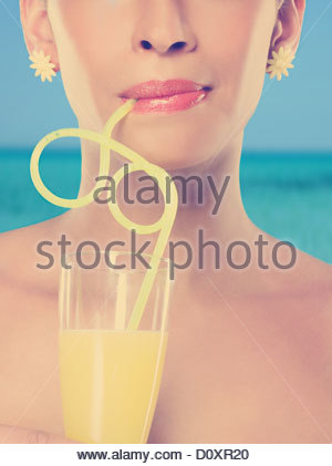 Young woman drinking glass of juice with curly straw - Stock Image