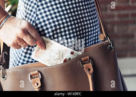 Close up photo of stylish woman taking money out the purse. - Stock Image