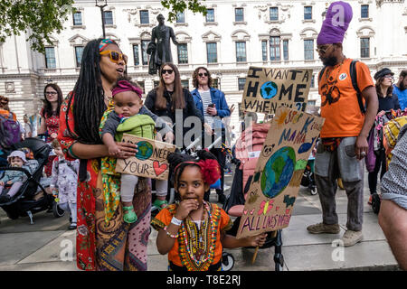 London, UK. 12th May 2019. People fill Parliament Square for a rally at the end of the XR International Mothers' Day March. A banner reads 'We are calling for the MOTHER of all uprisings.' The march was backing Extinction Rebellion's call for the drastic and urgent action needed to avert the worst consequences of climate change, including possible human extinction. Our politicians have declared a climate emergency but now need to take real action rather than continuing business as usual which is destroying life on our planet. Peter Marshall/Alamy Live News - Stock Image