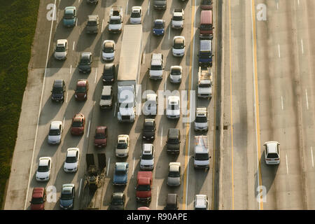 View of cars on a freeway in the evening rush hour, and one car on the opposite carriageway. - Stock Image