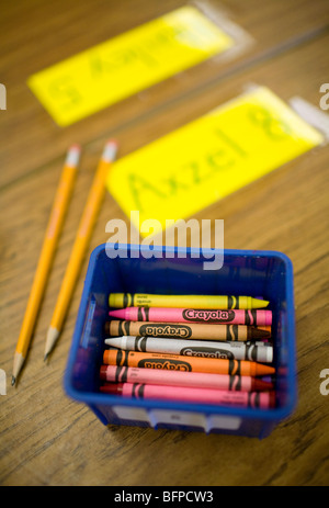 An assortment of crayons in a bin on a classroom desk. - Stock Image