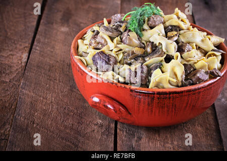 Venison or Beef Mushroom Stroganoff with in a red ceramic serving bowl garnished with fresh dill over a rustic wood table background. - Stock Image