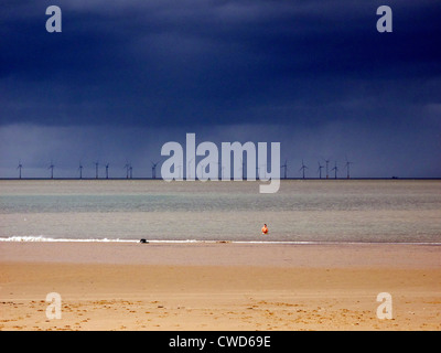 September 2011. Offshore wind farm beyond the beach at New Brighton, Wallasey, Merseyside. Man stands in water. - Stock Image
