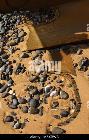 Old wrecked boat hatches and hull parts buried in the beach sand amongst stones, peebles and hull parts. - Stock Image