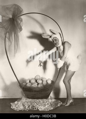 Woman in bunny costume with large basket of Easter eggs - Stock Image