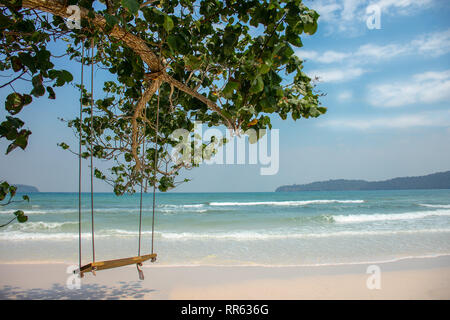 Basic tree hung swing in front of paradise island white sand beach with turquoise sea. - Stock Image
