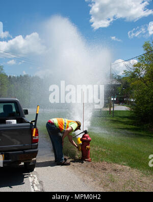 Village worker opening fire hydrant valve to flush out the water lines in Speculator, NY USA - Stock Image