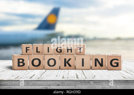 Flight booking sign at an airport with a plane in the background - Stock Image