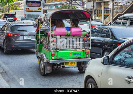 BANGKOK, THAILAND - NOVEMBER 2018: Auto rickshaw (tuk-tuk) with passengers on the street in the sunny day in Bangkok, Thailand - Stock Image