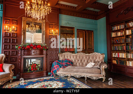 Luxury classic interior of home library. Sitting room with bookshelf, books, arm chair, sofa and fireplace. Clean and modern decoration with elegant f - Stock Image