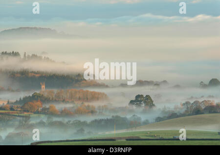 the tower of St Mary's Church at Dartington bathed in the first light of a winter's morning. - Stock Image