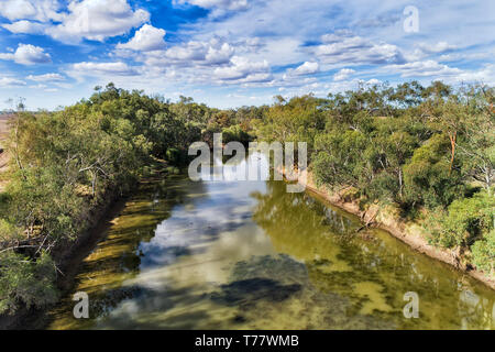 Small lazy fresh water Gwydir river in Narrabri shire around Moree town with gumtrees growing on shores under blue sky in arid climate of Australian o - Stock Image