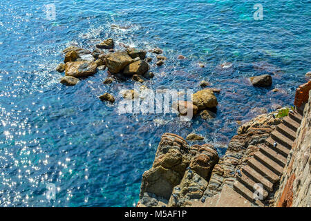 The rocky coastline of Cinque Terre Italy with the sun reflecting off the aqua blue shallow sea while pigeons play - Stock Image