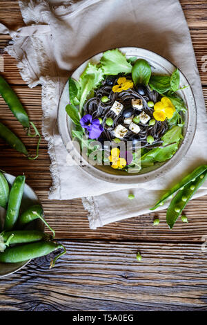 Vegetarian black bean pasta salad with leafy greens, olives, green peas, sheep cheese, decorated with edible flowers - Stock Image