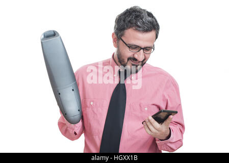 Smiling young man with handheld vacuum cleaner looking at his cell phone - Stock Image