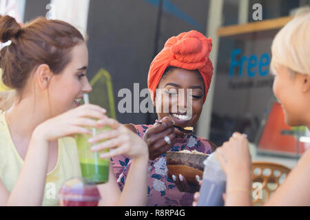 Young women friends drinking smoothies and eating at sidewalk cafe - Stock Image