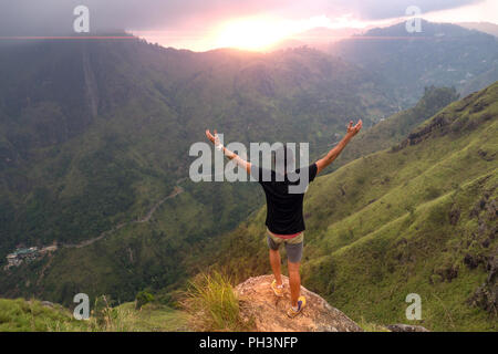 Hiker standing on top of a mountain with raised hands and enjoying sunrise - Stock Image