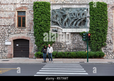 A couple wait to cross a street in the center of Verona, Italy - Stock Image
