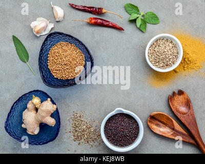 Various herbs and spices flat lay on concrete background. - Stock Image