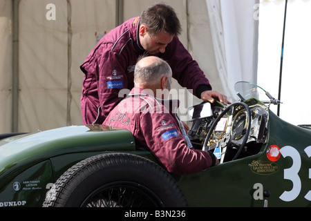 driver in a clssic racing car in the pit lane - Stock Image