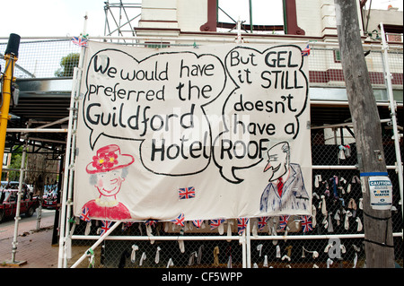 Sign linking visit to Australia of Queen Elizabeth to the lack of protection for the damaged Guildford Hotel - Stock Image