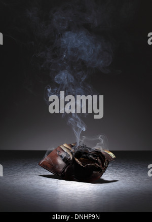 A burnt brown leather wallet filled with credit cards and money. - Stock Image