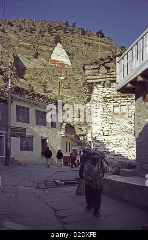 Porter walking down main street of Marpha in Kali Gandaki valley on Annapurna circuit Nepal - Stock Image