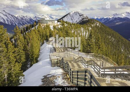 Wooden Boardwalk Stairs and Distant Snowcapped Peaks on Sulphur Mountain Gondola above City of Banff in Canadian Rocky Mountains - Stock Image