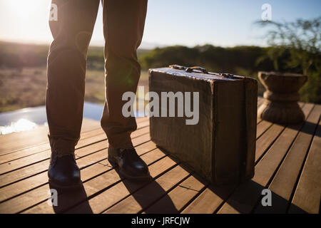 Low section of man with suitcase standing on deck - Stock Image