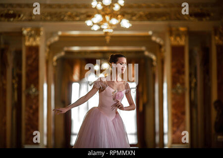 Beautiful ballerina dancing in a luxurious hall with a chandelier in a pink dress against the window. Closeup. - Stock Image