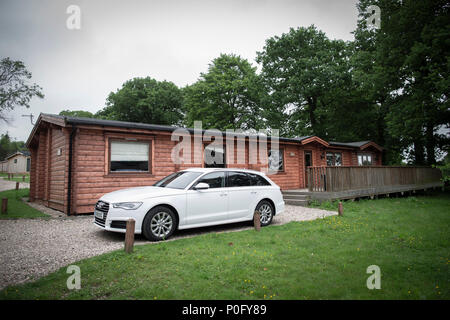 An Audi A6 Avant parked alongside a luxury log cabin retreat in the English countryside - Stock Image