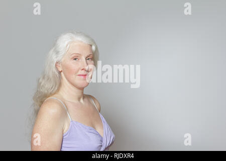 Headshot of a mature woman with freckles and shiny long gray hair in front of white background, copy space. - Stock Image