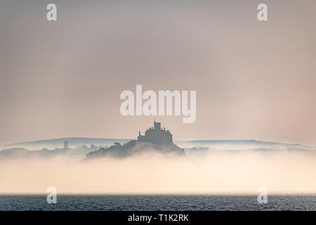 Penzance, Cornwall, UK. 27th Mar, 2019. UK Weather. Shortly after sunrise sea mist formed on the surface of the sea at Mounts Bay, shrouding the base of St Michaels mount. Credit: Simon Maycock/Alamy Live News - Stock Image
