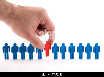 Man holds an employee in his hand. Personnel selection and management within the team. Dismissal and hiring people to work concept. - Stock Image