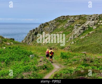 A young couple walking the south west coastal path,Lands End,Cornwall,England,UK - Stock Image