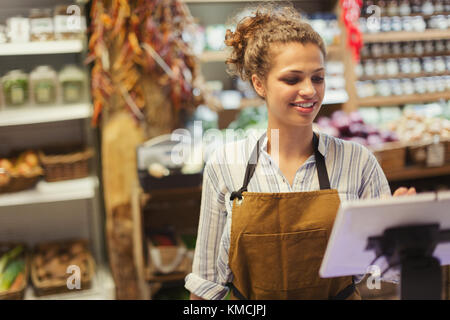 Female cashier using touch screen cash register in grocery store - Stock Image
