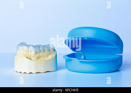 Grind guard on a custom-made tooth model, used against excessive wear caused by bruxism, with additional blue case - Stock Image