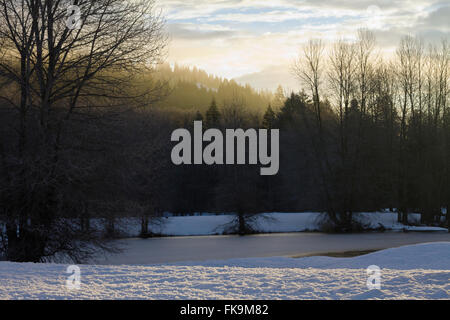 Sunrise over a frozen lake in the Pacific Northwest - Stock Image