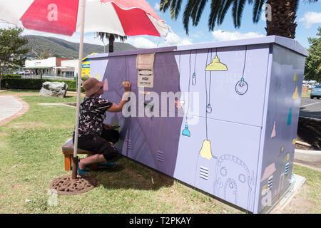 Lady volunteer adding artwork to electrical substation.Tamworth Australia - Stock Image