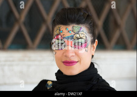 Venice, Italy. 25th Feb, 2014. Not every mask is made of paper mache. Many stalls are set up to paint masks onto the faces of Carnivale attendees. This lady is a mask painter. Venice Carnivale Credit:  MeonStock/Alamy Live News - Stock Image