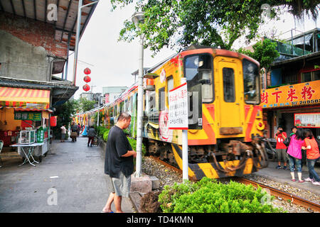 SHIFEN, TAIWAN - JUL 15, 2013: A moving train passes through the narrow passage of Shifen Old Street in this famous town near Taipei, Taiwan, where vi - Stock Image