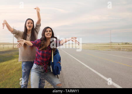 Two women standing on a highway waving hands for a lift - Stock Image