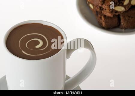 White porcelain cup with drinking chocolate. Almond and chocolate biscoti in background. Studio shot.      Ref: CRB538_103609_0017  COMPULSORY CREDIT: - Stock Image